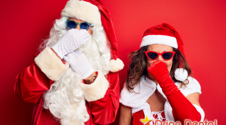 Orion Dental :: Mr. and Mrs. Claus holding noses bad breath